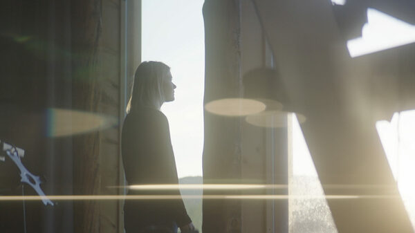 Micah Atkins stands at a window looking out as the sun begins to set. There is a glare from the sun that cuts across the screen.
